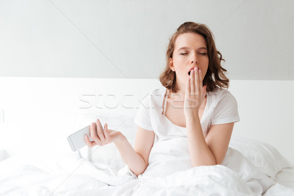 Bored young woman in bed indoors with eyes closed yawning Stock photo © deandrobot