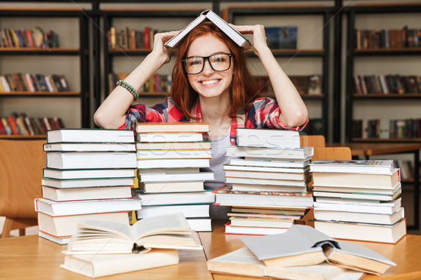 Happy teenage girl sitting at the library Stock photo © deandrobot