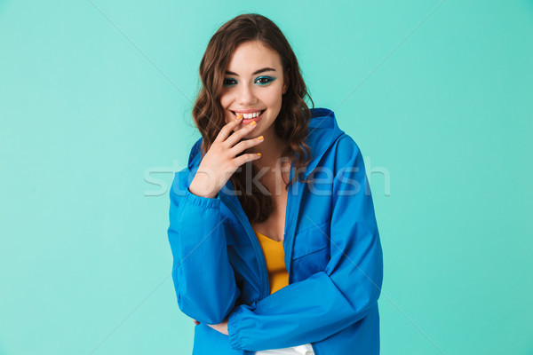 Photo of joyous pretty woman 20s wearing raincoat or jacket smil Stock photo © deandrobot