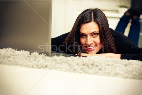 Portrait of a middle-aged cheerful woman lying with laptop at home Stock photo © deandrobot