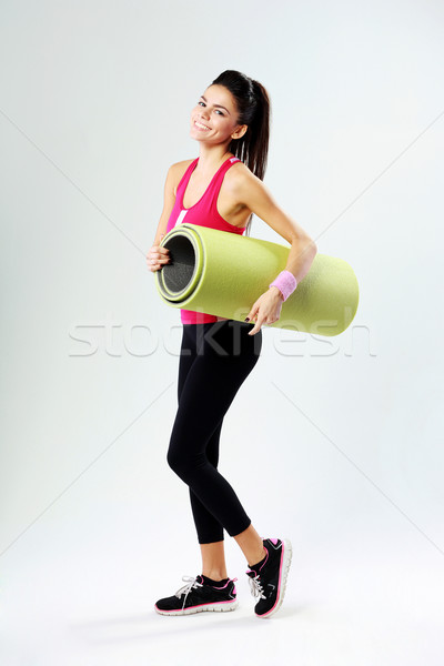 Young sport woman with yoga mat on gray background Stock photo © deandrobot
