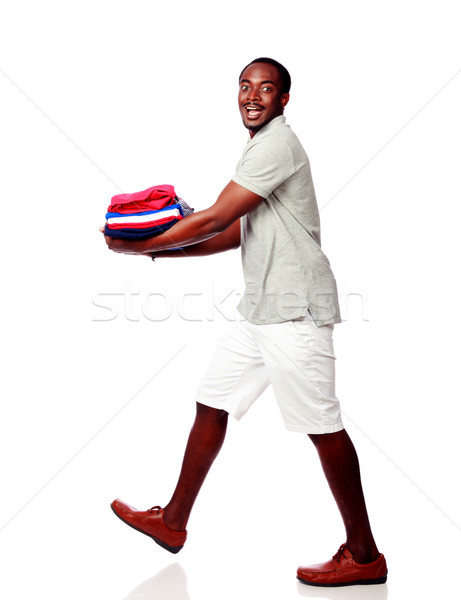 Studio shot of a happy african man holding his clothes over white background Stock photo © deandrobot