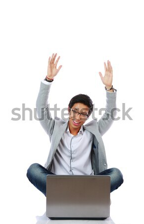 Excited Asian man using laptop on the floor over white background Stock photo © deandrobot