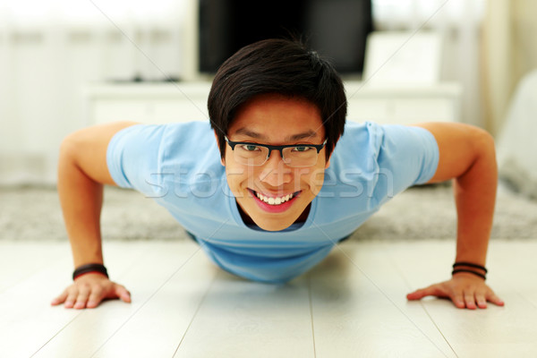 Portrait of a happy young man doing push ups in the living room at home Stock photo © deandrobot
