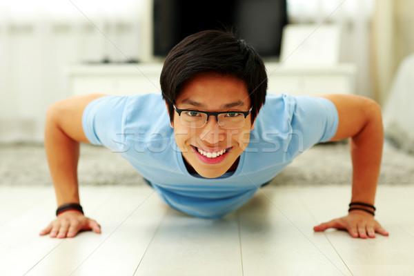 Retrato feliz joven flexiones salón casa Foto stock © deandrobot