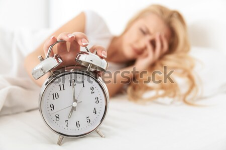 Happy woman waking up in the morning and looking on alarm clock. Focus on clock Stock photo © deandrobot