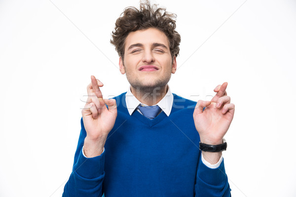 Young man with crossed fingers over white background Stock photo © deandrobot