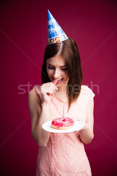 Peinzend jonge vrouw donut kaars roze Stockfoto © deandrobot
