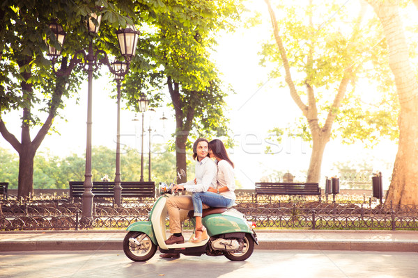 Sideview of a trendy couple riding a scooter in the morning. Sun is shining through trees Stock photo © deandrobot