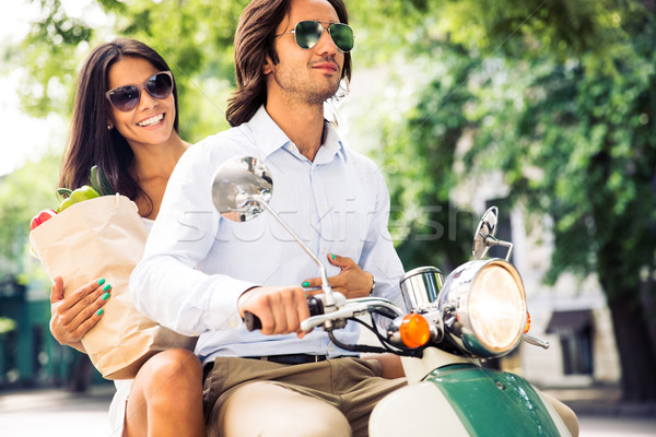 Happy young couple driving scooter while woman holding bag full of groceries. Summer time. Stock photo © deandrobot