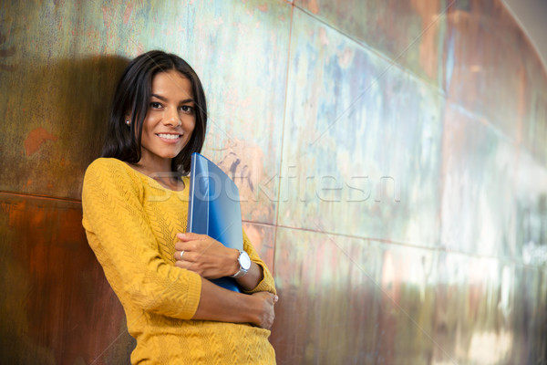 Businesswoman standing with folder in hallway  Stock photo © deandrobot