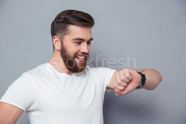 Smiling man looking on wrist watch Stock photo © deandrobot