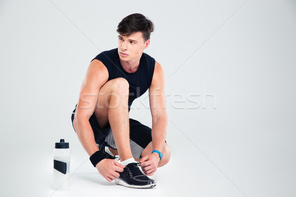 Stock photo: Athletic man tie shoelace