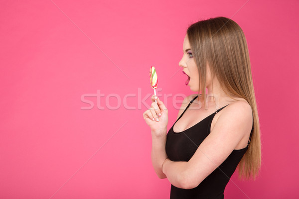 Young attractive surprised woman with lollipop Stock photo © deandrobot
