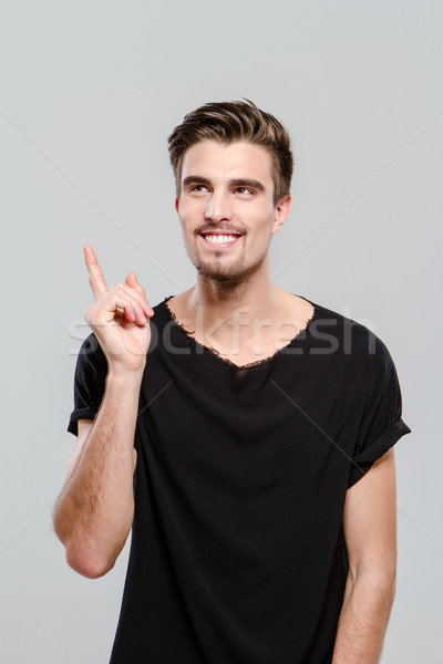 Portrait of young man having an idea and pointing up Stock photo © deandrobot
