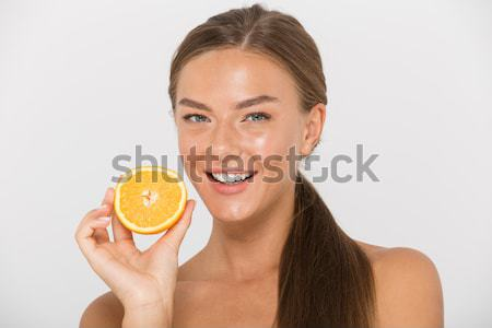 Positive pretty young redhead woman showing half of orange Stock photo © deandrobot