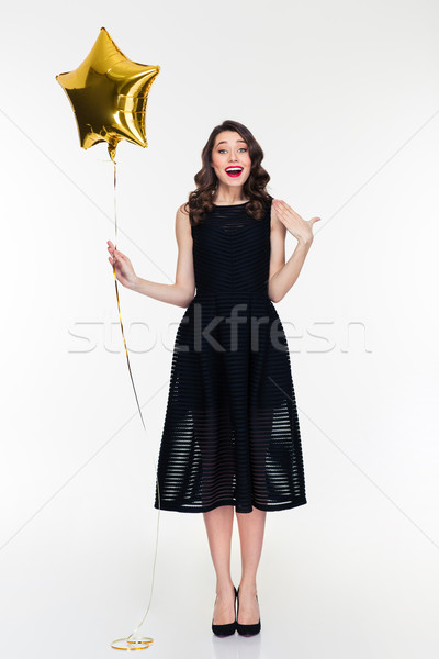 Stock photo: Surprised retro styled young woman with golden star shaped balloon