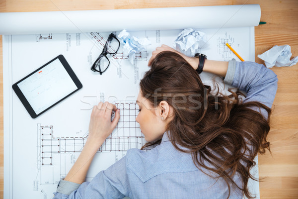 Tired young woman lying and sleeping on blueprint Stock photo © deandrobot