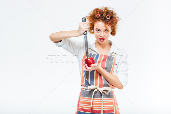 Housewife cutting apple with big knife Stock photo © deandrobot