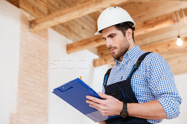 Happy builder writing notes in hardhat with clipboard Stock photo © deandrobot