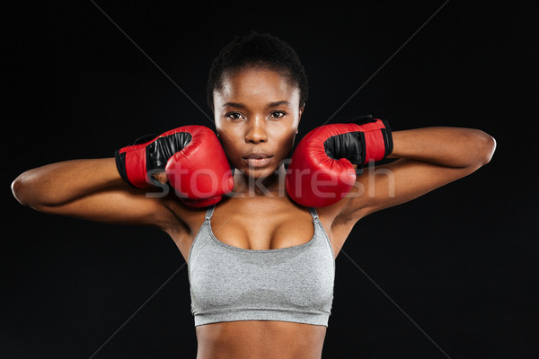 Portrait of a beautiful fitness woman standing in boxing gloves Stock photo © deandrobot