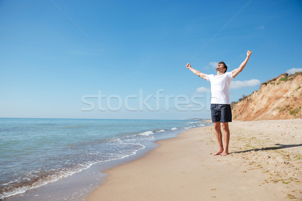 Happy man standing barefoot on the beach with hands outstretched Stock photo © deandrobot