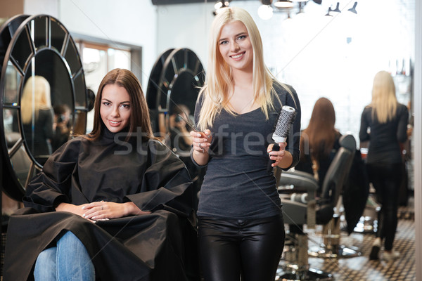 Young blonde female hairdresser holding scissors and comb Stock photo © deandrobot