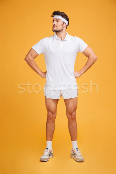 Handsome confident young man athlete standing with hands on hips Stock photo © deandrobot