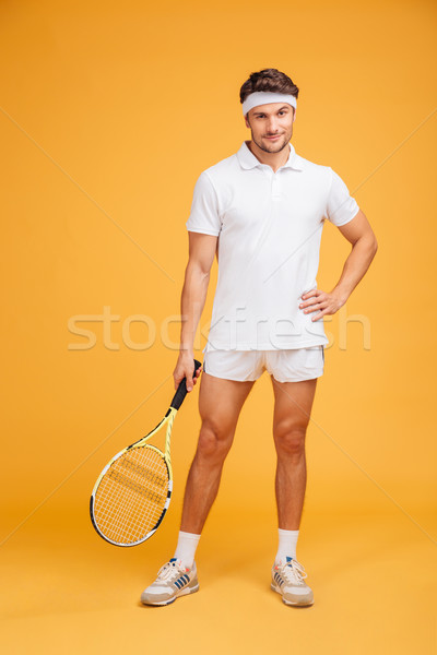 Attractive young man tennis player standing and holding racket Stock photo © deandrobot