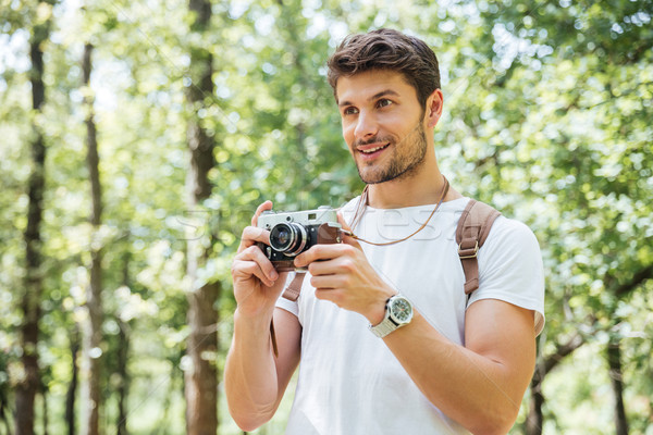 Happy man taking pictures with old photo camera in forest Stock photo © deandrobot