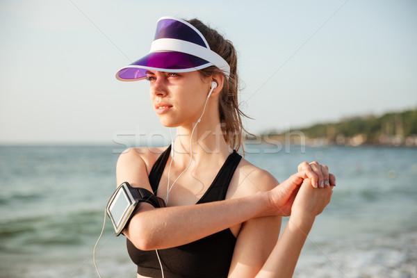 Fitness runner doing warm-up routine on beach before running Stock photo © deandrobot