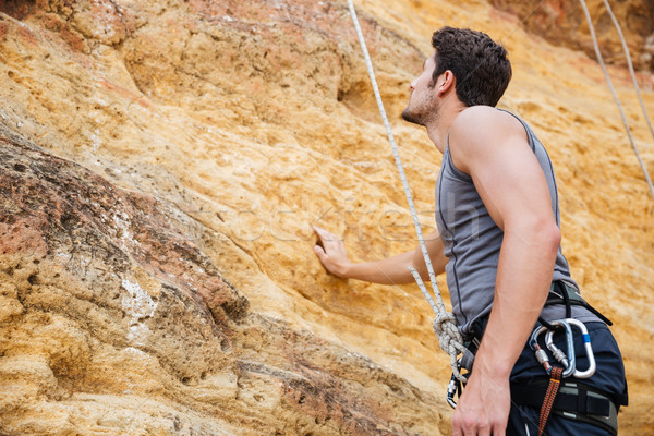 Young handsome sportsman getting ready to climb a cliff Stock photo © deandrobot