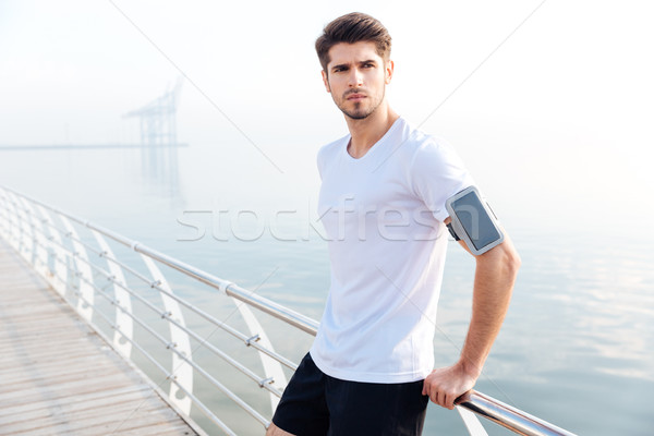 Confident sportsman with cell phone on armband standing at pier Stock photo © deandrobot