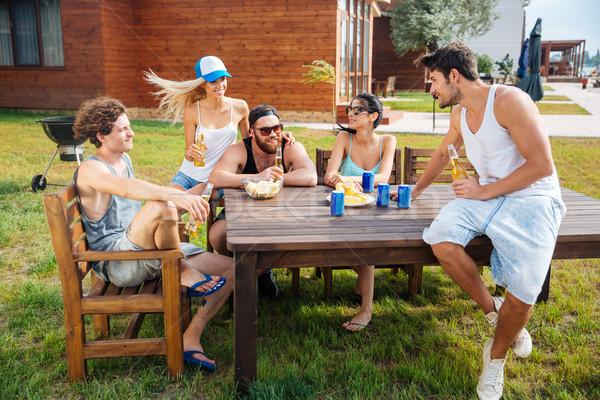 Csoport boldog fiatalok ül iszik sör Stock fotó © deandrobot