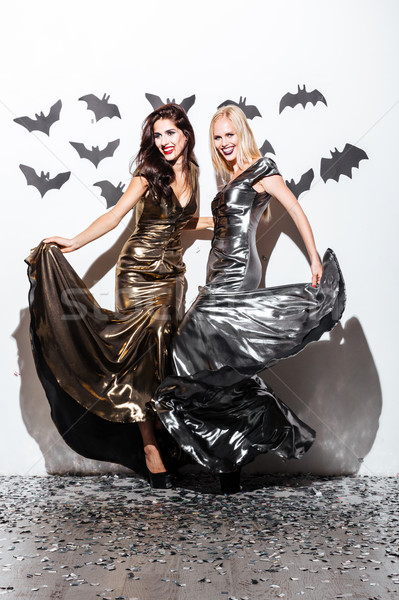 Two cheerful young women with halloween vampire makeup on party Stock photo © deandrobot