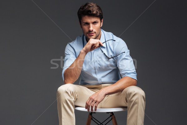 Handsome young man holding sunglasses sitting on the chair Stock photo © deandrobot