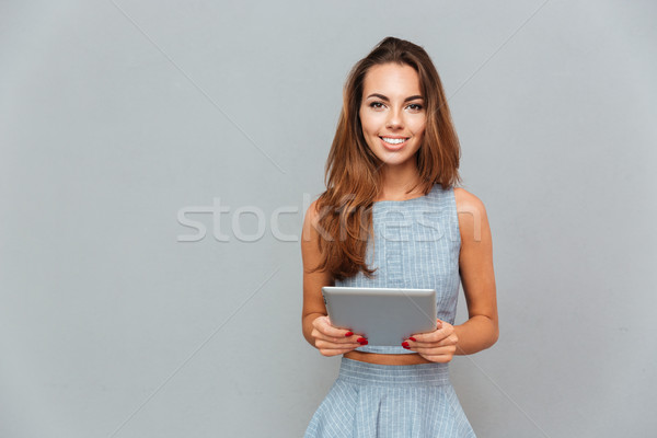 Portrait of happy lovely young woman standing and using tablet Stock photo © deandrobot