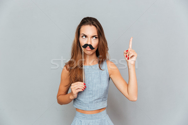 Serious amusing young woman with moustache props pointing up Stock photo © deandrobot