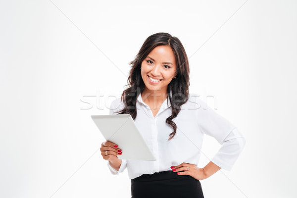 Smiling asian businesswoman standing with tablet computer Stock photo © deandrobot