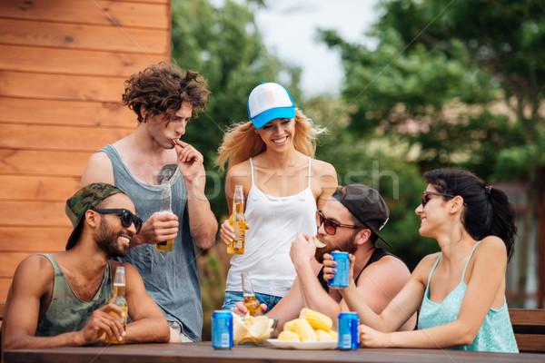 Szczęśliwy młodych ludzi jedzenie pitnej odkryty grupy Zdjęcia stock © deandrobot