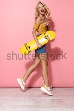 Jeunes souriant brunette femme posant skateboard Photo stock © deandrobot