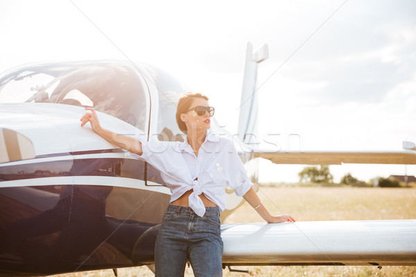 Beautiful young woman standing near private plane Stock photo © deandrobot