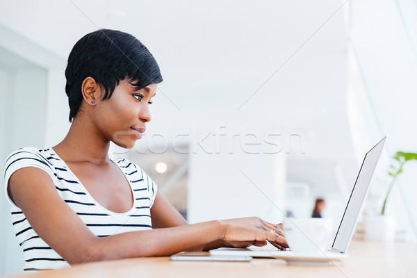 Attractive african businesswoman working with laptop and drinking coffee Stock photo © deandrobot