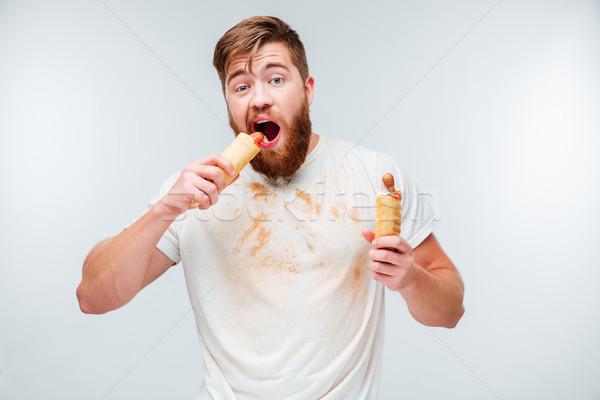 Hungry bearded man in dirty shirt biting hotdog Stock photo © deandrobot