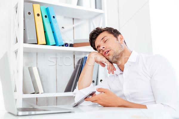 Kimerült fiatal üzletember alszik ül irodai asztal Stock fotó © deandrobot