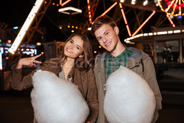 Happy young couple with cotton candy in amusement park Stock photo © deandrobot
