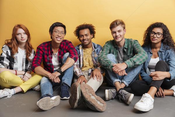 Több nemzetiségű csoport boldog fiatalok ül együtt Stock fotó © deandrobot