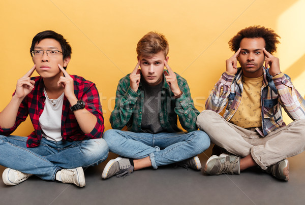 Three tensed stressed young men friends sitting and touching temples Stock photo © deandrobot
