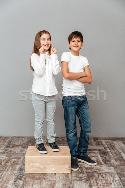 Girl standing on box near tall boy and celebrating success Stock photo © deandrobot