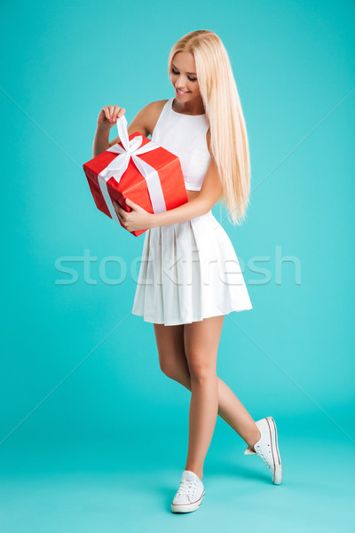 Happy smiling woman in casual clothes opening gift box Stock photo © deandrobot